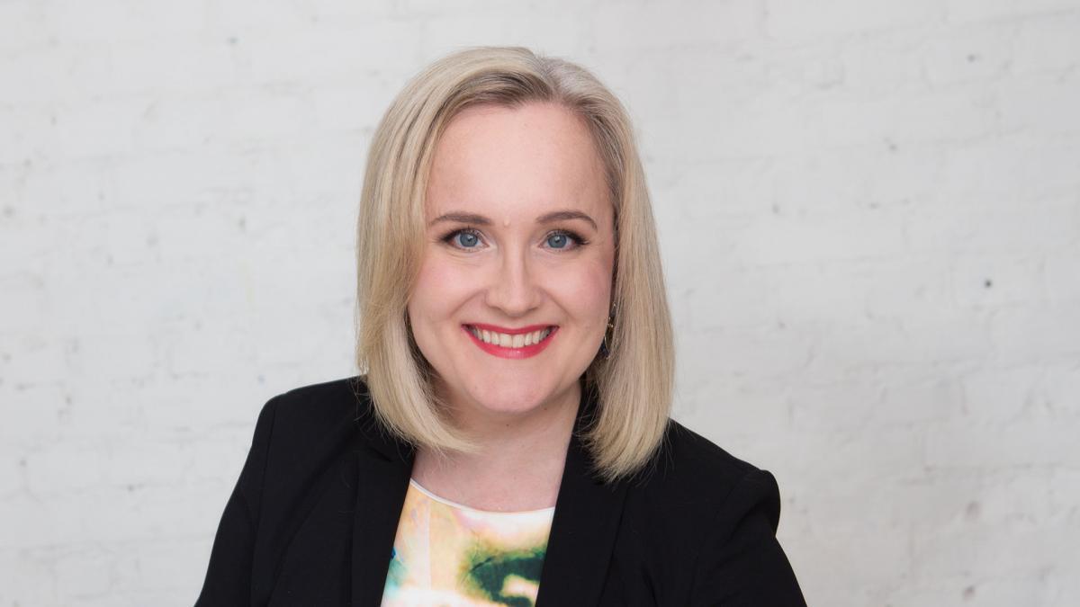 Eveliina Sumelius-Lindblom poseeraa valkoista seinää vasten studiossa ja hymyilee.