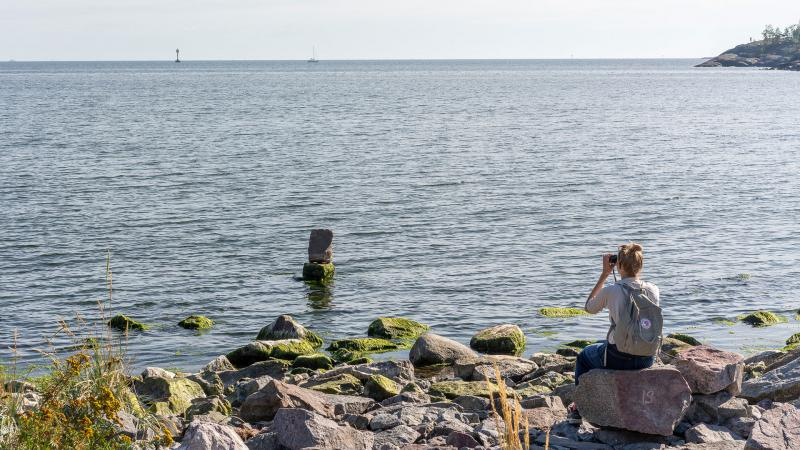 Person sitting on a rock by a shore, looking through binoculars at a rock installation at a distance in shallow water