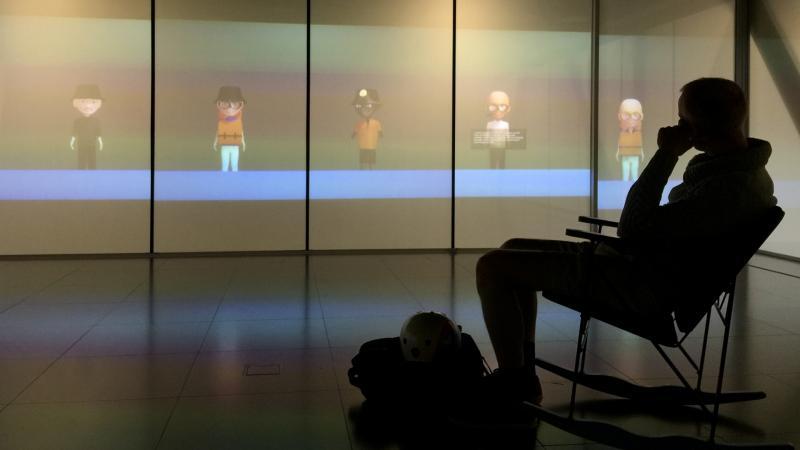Henkilö katsoo mediataideteosta näyttelyssä. Kuva: Soila Hänninen