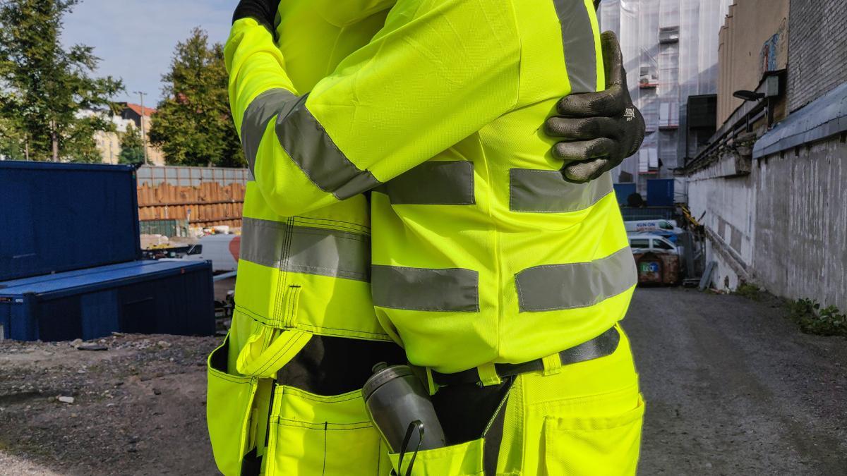 Kuvassa kaksi neonkeltaisiin asuihin pukeutunutta henkilöä halaa toisiaan.