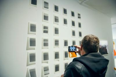 Henkilö ottaa valokuvaa taideteoksesta seinällä.