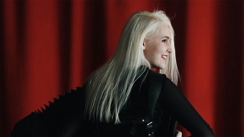 Ilona Viitala poseeraa harmonikan kanssa punaisen esiripun edessä. Selkä kameraan päin ja hän hymyilee.