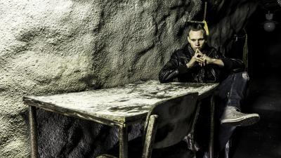 Markus Laine istuu pöydän ääressä hämärässä. Markus on mietteliään näköinen