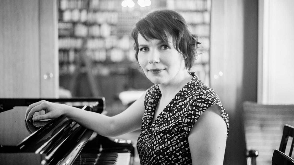 Jenni Lappalainen poseeraa pianon edessä.