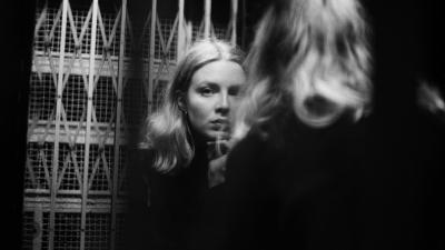Lina Sandvik katsoo hissin peilin kautta suoraan kameraan.