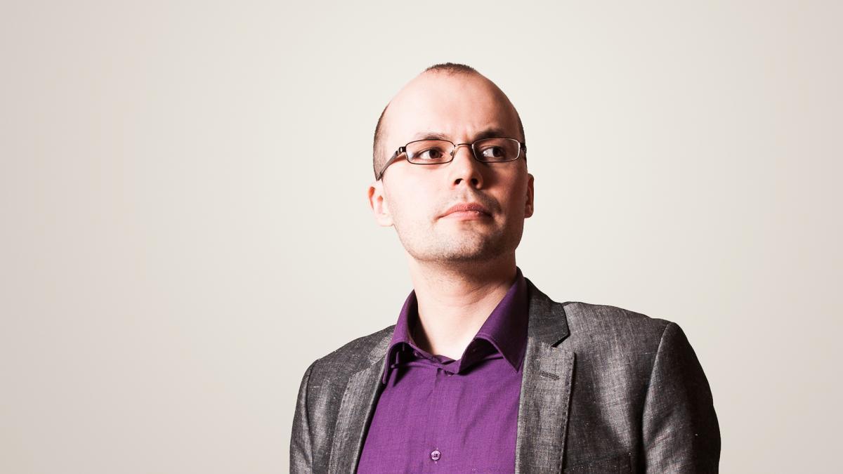Kirill Kozlovsky poseeraa valkoista taustaa vasten ja katsoo oikealle kameran ohi.