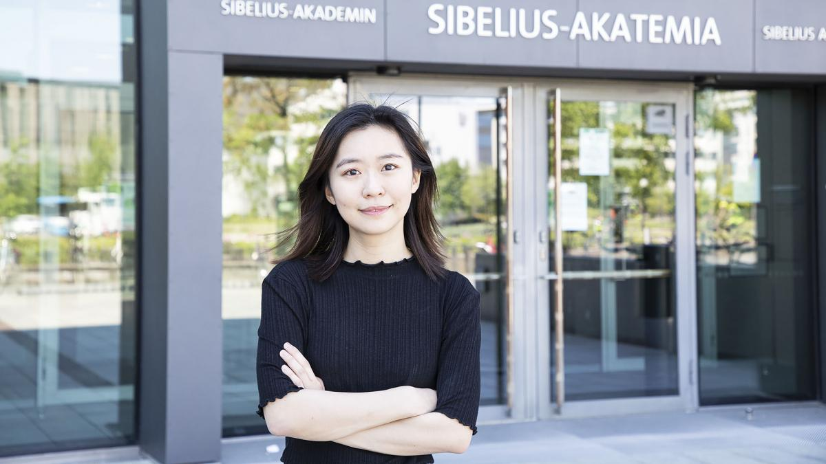 Adele Xiang standin in front of the Sibelius Academy's entrance.
