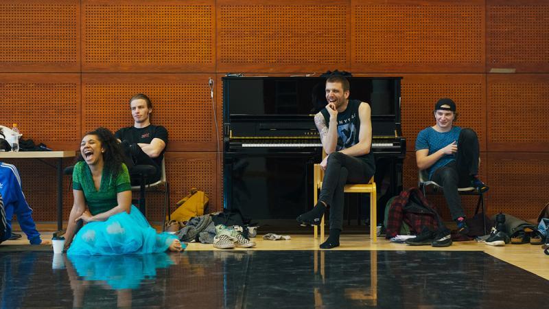 Neljä opiskelijaa istuvat tuoleilla tai lattialla opetustilassa. Taustalla musta piano.
