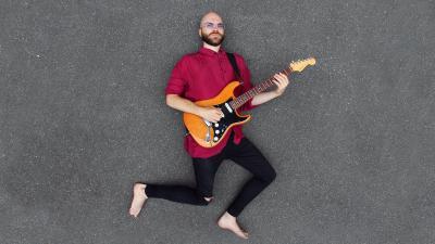Lassi Övermark makaa maassa ja soittaa kitaraa