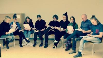 yhdekstän ihmistä istuu ja lukee. KAikilla on papereita käsissä.