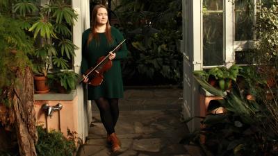 Maisa Saari poseeraa viulun kanssa viherkasvien seassa.