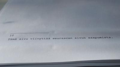 Kuvassa valkoinen paperi, jonka alareunassa tekstiä.