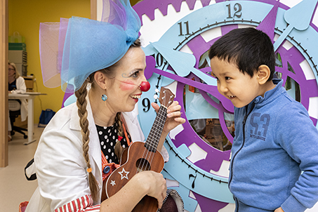 A hospital clown plays the guitar with a young patient. A hospital staff member sits in an office in the background.