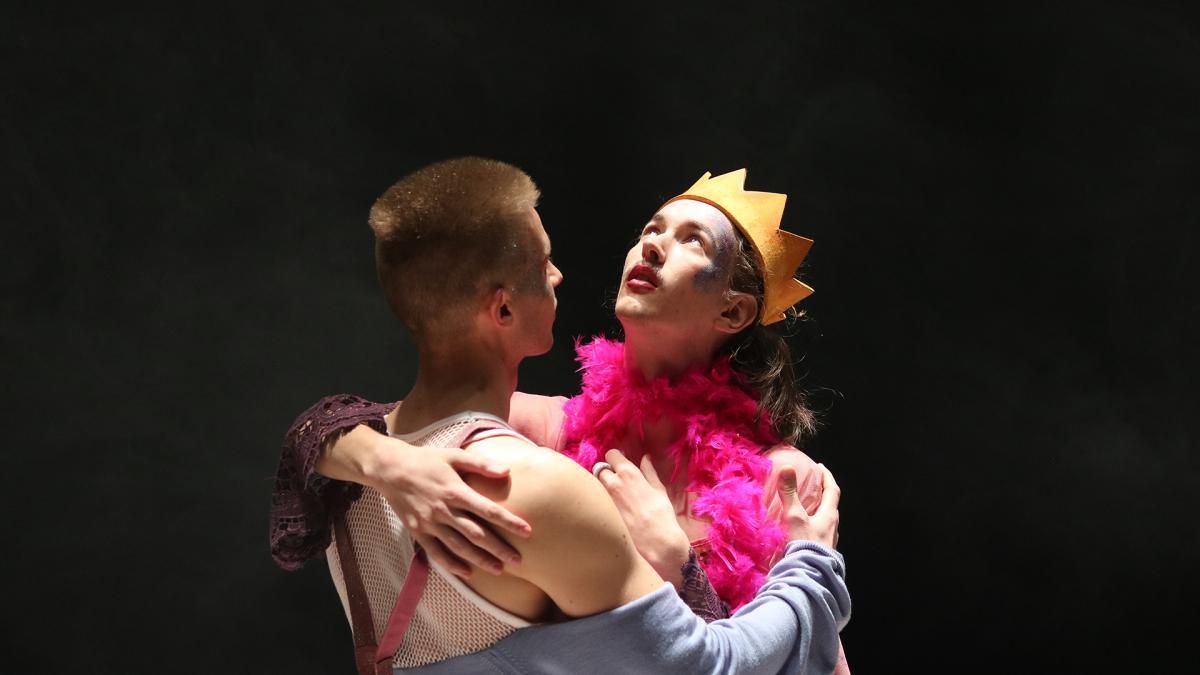 Kuvassa kaksi henkilö syleilee, toisella on kruunu päässä.