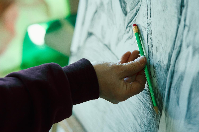 Käsit pitää kynää canvaksen edessä