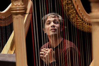 Emmanuel Ceysson pictured between the strings ​​of a harp.
