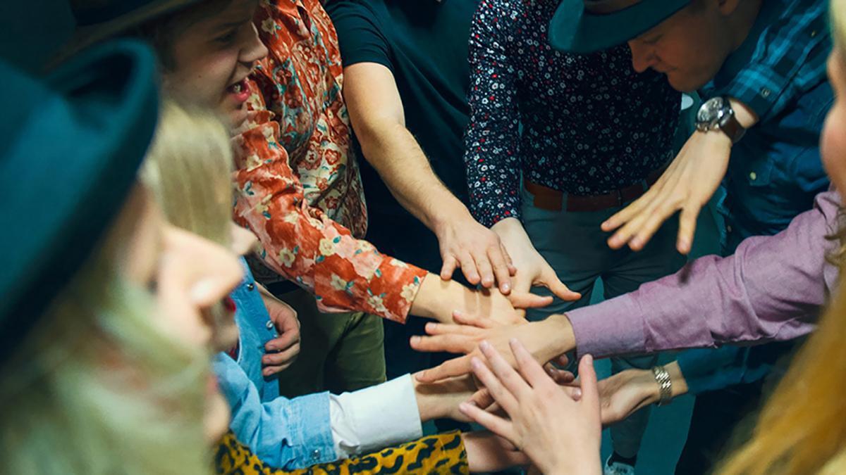 Ryhmä oppilaita on laittanut kätensä päällekkäin ja valmistautuu tsemppihuutoon.