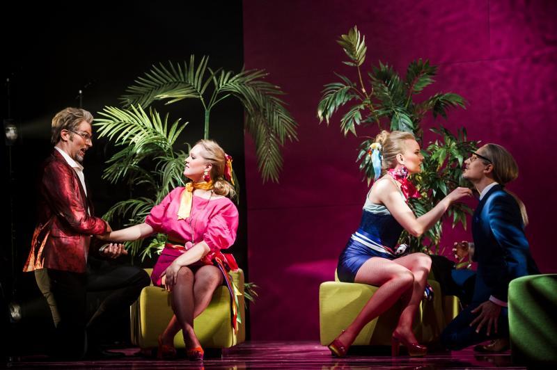Kaksi naista ja miestä laulavat toisilleen värikkäässä oopperalavastuksessa