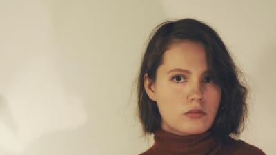 Selma Savolainen seisoo valkoisen seinän edessä vakava ilme kasvoillaan. Kuva on rajattu hartioista. Hänen varjonsa heijastuu seinälle.