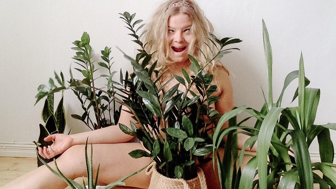 Keskellä vaaleatukkainen henkilö, jolla on viherkasveja edessään, sivuillaan ja takanaan.