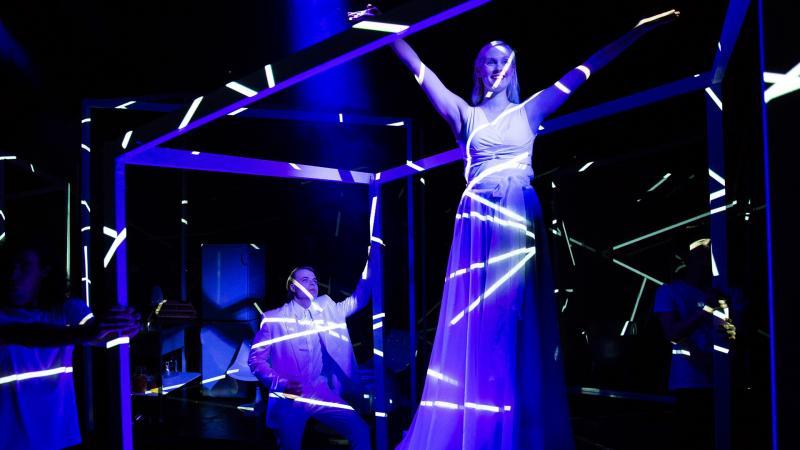 Lavalla kaksi näyttelijäopiskelijaa tummansinisessä valaistuksessa, joista toinen seisoo kuution muotoisen kehikon sisällä.