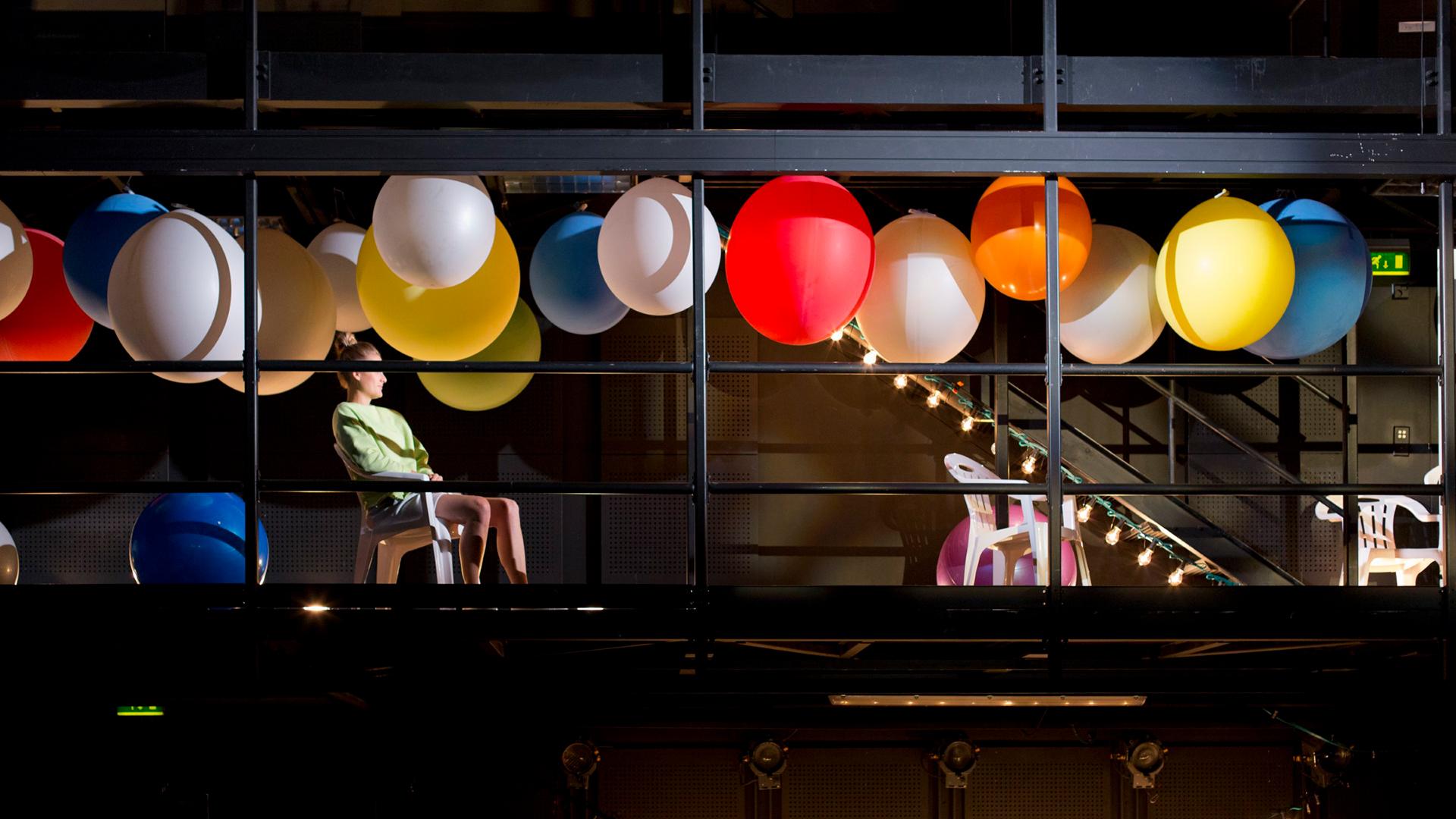 Esiintyjä kuvan vasemmassa reunassa istuu tuolilla lavarakennelmassa, joka on lähellä katonrajaa. Katosta roikkuu suuria erivärisiä ilmapalloja. Taustalla keijuvaloja.