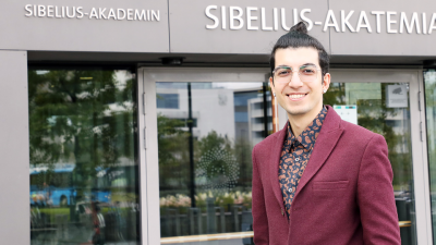 Ahoora Hosseini is smiling in fornt of the enteance of Sibelius-Academy