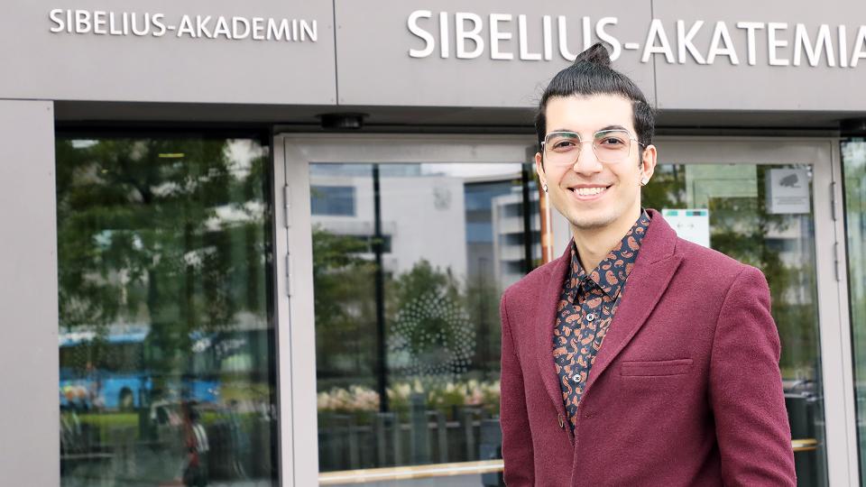 Ahoora Hosseini is smiling in fornt of the enteance of Sibelius-Academy