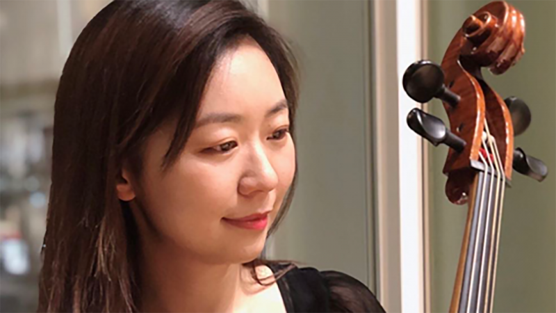 Adele Xiang is smiling while holding her cello.