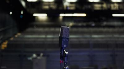 A microphone photographed in front of an empty audience. The image is dark.