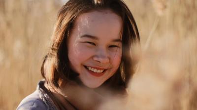 Aino Yamaguchi hymyilee kameralle. Kuva on otettu viljapellon keskellä.