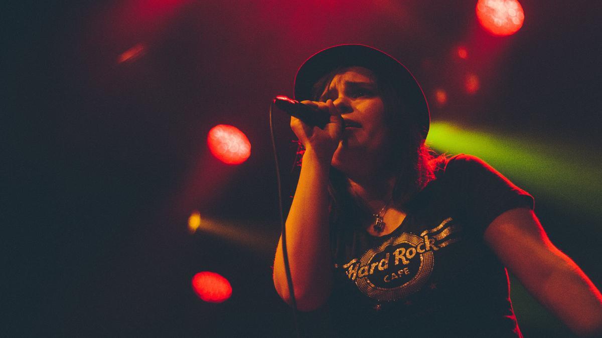 Sarah Devoyon laulaa lavalla. Kuva on otettu alhaalta päin ja taustalla on punaisia sekä vihreitä spotlight -valoja.