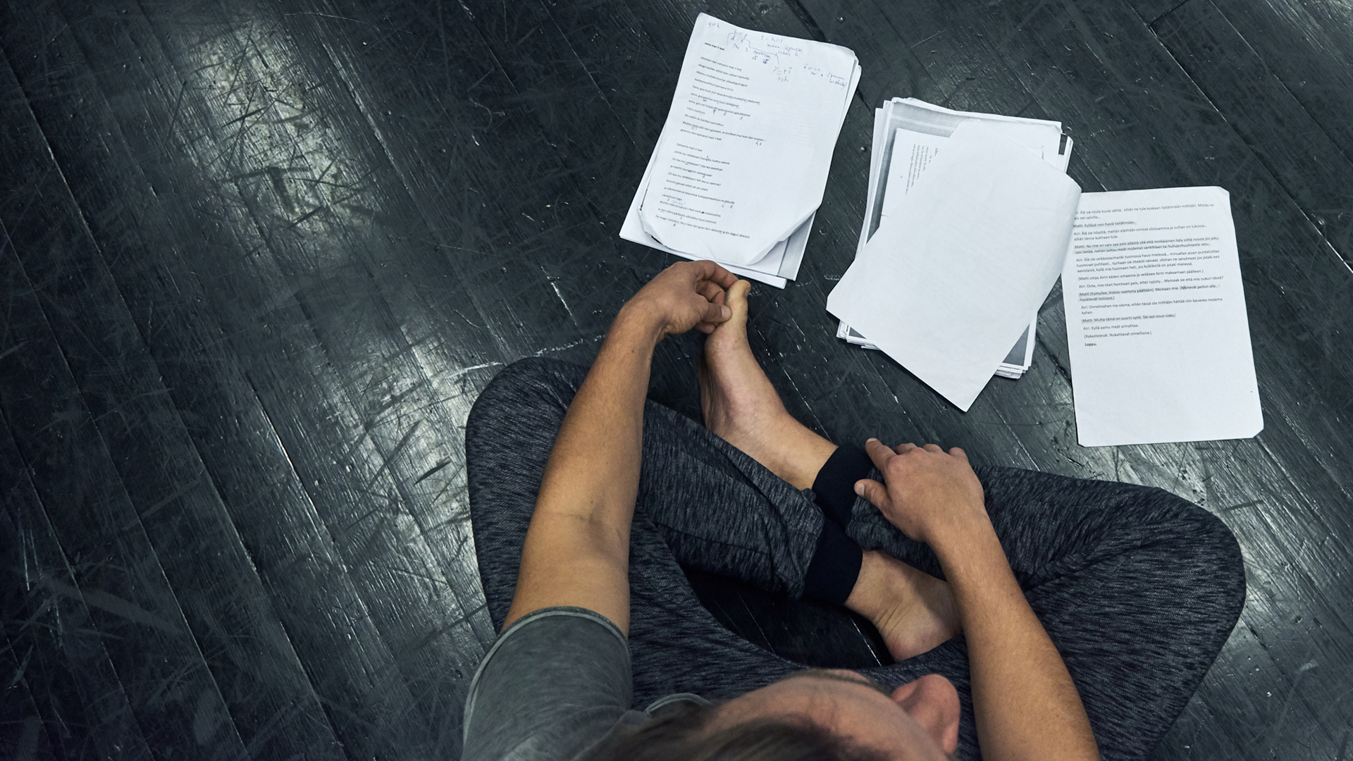 Person sitting cross-legged on black floor, papers with text placed on the floor.