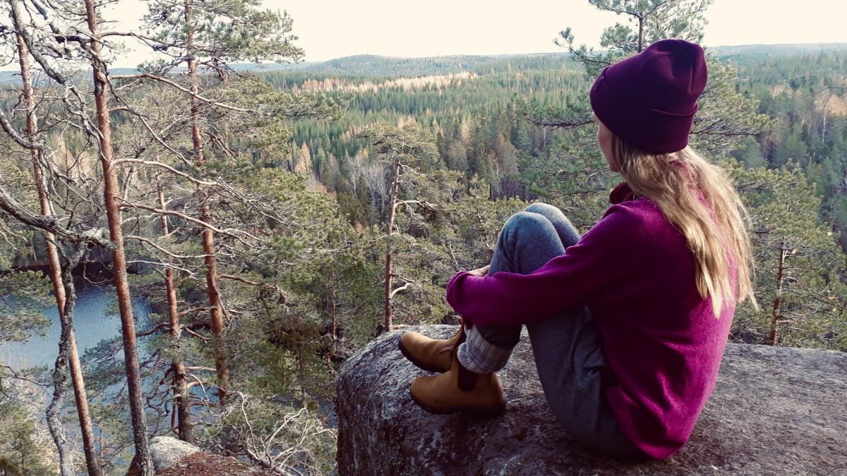 Eerika Grof istuu kalliolla selkä kameraan päin. Taustalla näkyy perinteistä suomalaista kansallismaisemaa, vettä ja metsää.