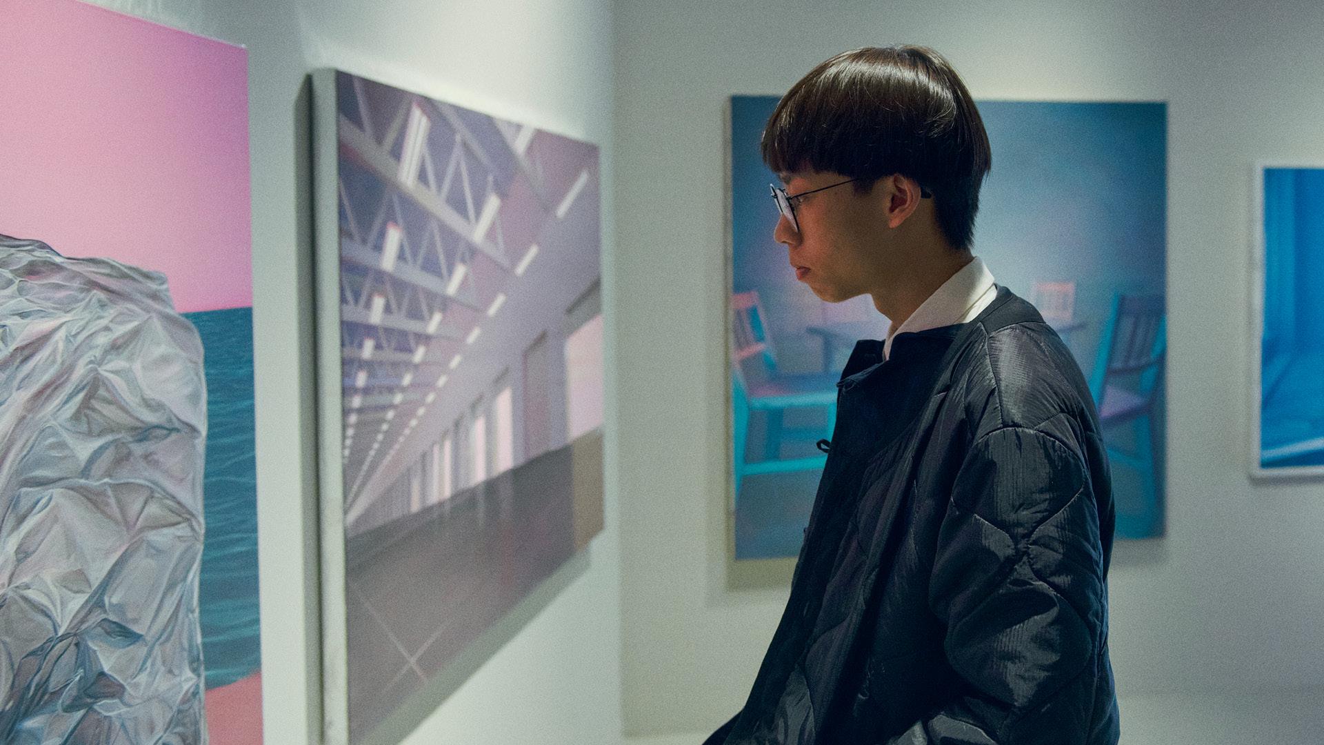 Henkilö tutkii Kuvataideakatemian näyttelyn töitä