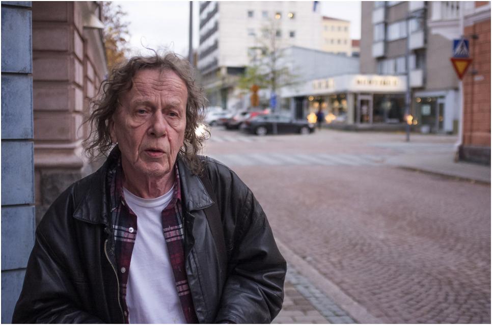 Jukka Ruohomäki stands on the corner of the street and looks past the camera.
