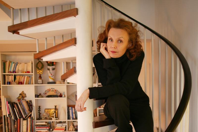 Säveltäjä Kaija Saariaho istuu portailla ja nojaa käteensä.