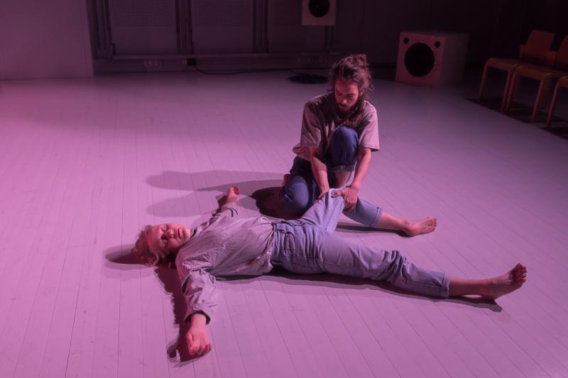 Esiintyjää vetää toisen esiintyjän, joka makaa lattialla, jalasta.