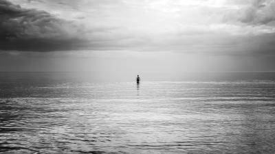Mustavalkokuva rannalta merelle päin, keskellä kuvaa ihminen seisoo vedessä.