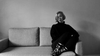 Pinja Savijärvi istuu sohvalla katse kohti kameraa mustavalkoisessa kuvassa.Taustalla on valkoinen seinä, huone on tyhjä. Pinjalla on vakava ilme kasvoillaan.