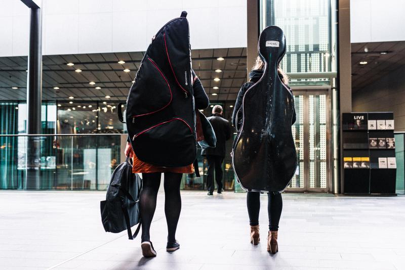 Kaksi henkilöä kävelee isot viulukotelot selässään