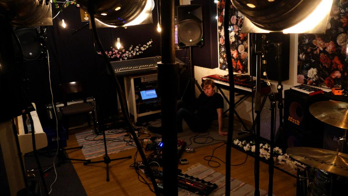 Elias Riipinen is sitting on the floor of a studio. The photo is taken behind some lights.