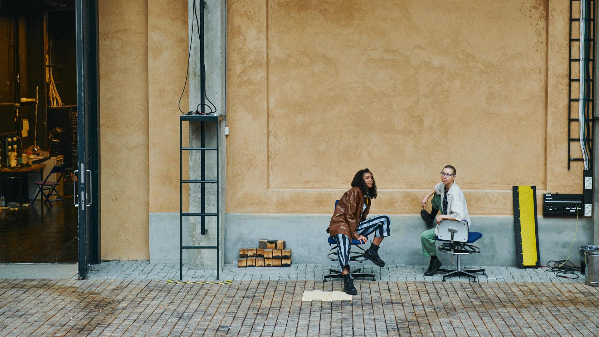 Kaksi maisteriopiskelijaa istuvat Teatterikorkeakoulun rakennuksen ulkopuolella.