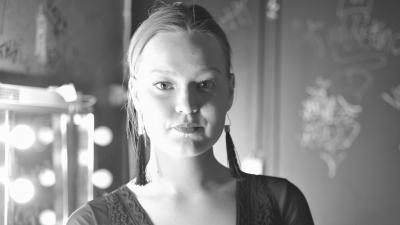 Riina Huttunen poseeraa mustavalkoisessa kuvassa, katse suoraan kameraan. Taustalla on peili.