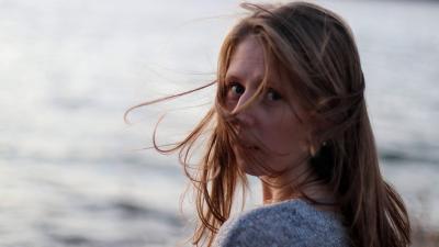 Susanna Sandell katsoo kameraan meren rannalla.