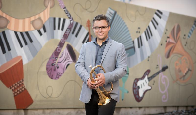 Peter Roos seisoo graffitin edessä, jossa on eri instrumentteja ja hymyilee. Käsissään hänellä on puhallinsoitin.