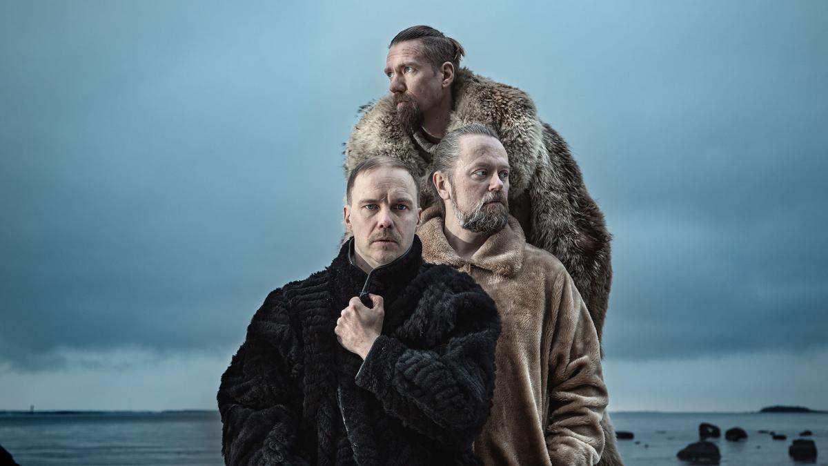 Ruska Ensemble poseeraa meren rannalla talvisella kelillä. Kuvassa on vahva kontrasti. Yhtyeen jäsenillä on turkikset päällä.