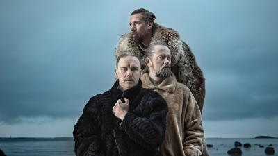 Ruska Ensemble is posing with fur coats on. Behing the ensemble there is sea or lake. It's winter and people on the picture are looking a bit cold.