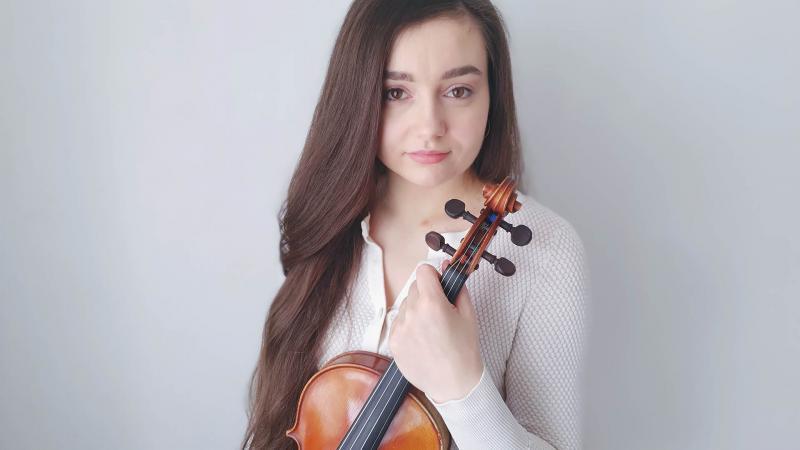 Kaia Voitka on kuvassa viulu käsissään. Hän katsoo suoraan kameraan ja seisoo valkoista seinää vasten.