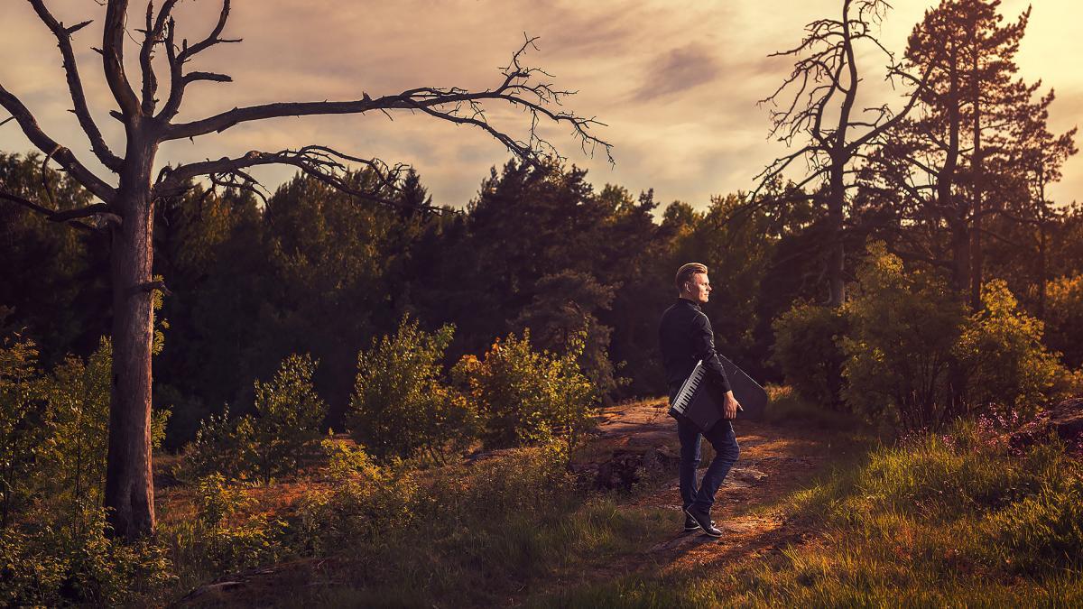 Aki Rissanen seisoo aukealla metsäalueella kannettavan keyboardin kanssa. Kuva on otettu auringonlaskun aikaan loppukesästä.